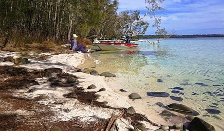 A woman seated on a lakeshore near a moored motorboat looks out over clear waters to a distant shore. Photo credit: Peter Smee © Manning Valley Adventures
