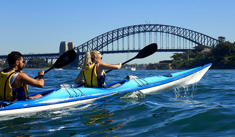 A man and woman paddle a double kayak on Sydney Harbour with the Sydney Harbour Bridge in the background. Photo credit: Matt Bezzina © Paddle Pirates