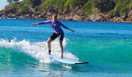A young woman rides a wave on turquoise waters at Byron Bay. Photo © Mojosurf
