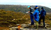 A group of hikers studies navigational aids in rugged terrain in Blue Mountains National Park. Photo credit: Ashley Burke © MountainSphere Adventures and Education