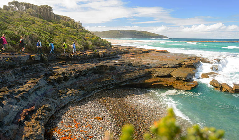 A group of bushwalkers trek toward a rocky point alongside turquoise ocean waters. Photo © Region X