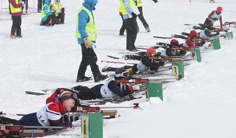A group of biathlon skiers lie in a line across the snow for target practice, with instructors standing behind them. Photo © NSW Biathlon