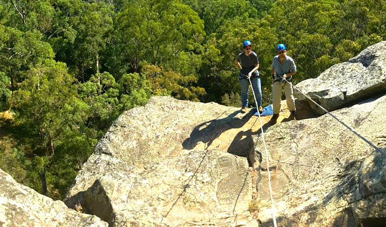 2 people in helmets manage climbing ropes as they stand near the top of a steep rock face. Photo credit: Peter Vaughan © Out and About Adventures