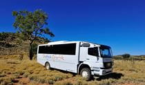 Outback Spirit tour bus set in an outback landscape of dry shrubland and hills. Photo credit: Steve Strike © Outback Spirit