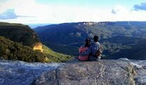 A couple seated on a rocky ledge gaze out over a vista for forest-clad mountains and valleys In Blue Mountains National Park. Photo credit: Dave Hadari © Oz Trails