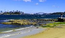 Coastal vista of rocky foreshore, with the Sydney CBD and Sydney Harbour Bridge in the background. Photo credit: Ben Barry © Personalised Sydney Tours