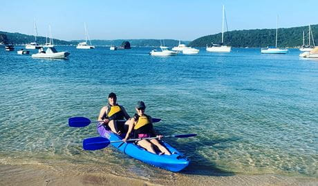 View of 2 people in a double kayak at the shore of a sandy bay, with boats in the background. Photo credit: Greg Moran © Pittwater Kayak Tours