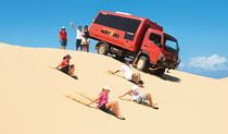 A group enjoys sand boarding on the dunes alongside a red Port Stephens 4WD Tours vehicle. Photo credit: Ray Alley © Port Stephens 4WD Tours