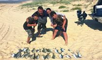 A family shows off their catch of fish on a beach. Photo credit: Tony Neill © Port Stephens Beach Fishing Safaris