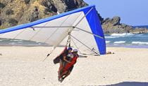 A tandem hang glider about to land on a beach next to to a rocky headland. Photo © Pro Flyte