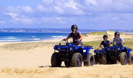 3 people wearing helmets ride blue quad bikes along coastal dunes. Photo © Quad Bike King