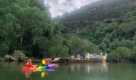 4 people in a 2 double kayaks paddle near a historic shipwreck on the Lower Hawkesbury River. Photo credit: Daniel Morrison © River Adventures