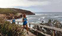 A group of runners jogs across a cliffside boardwalk in Bouddi National Park with expansive ocean and coastal views. Photo © Tiffany Alexandria Photography