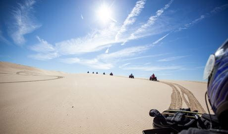 Quad bikers riding on Worimi sand dunes. Photo: Sand Dune Adventures
