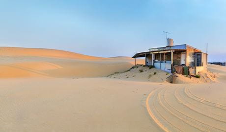 A Tin City shack set in the pristine landscape of Stockton sand dunes, in the Worimi Conservation Lands near Port Stephens. Photo © Andrea Drury