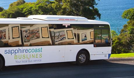View of bus emblazoned with Sapphire Coast Buslines logo on a coastal road. Photo © Angi High