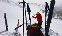 A man in winter outdoor clothing using an avalanche probe on a snow-covered mountain slope. Photo credit: Adam West © Snow Safety Australia