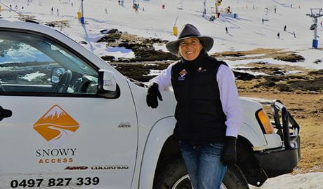 A smiling woman leans on a white vehicle emblazoned with the Snowy Access logo, with ski fields in the background. Photo © Claire Rogerson