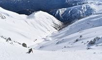 A lone skier descends into a snow-covered mountain valley. Photo credit: Rohan Kennedy © Snowy Mountains Backcountry