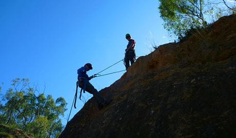 Silhouetted climbers with ropes on a rocky slope. Photo credit: Chris Brown © Snowy Mountains Climbing School