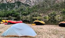 Rafts and a tent pitched by the Snowy River on a guided tour with Snowy River Expeditions in Kosciuszko National Park. Photo: © Snowy River Expeditions