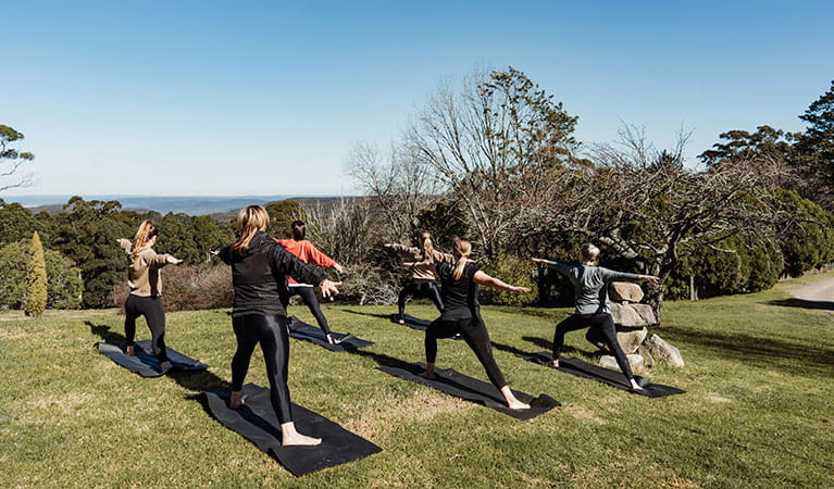 A group of people doing yoga at Solar Springs Retreat overlooking Morton National Park. Photo: Translucent Photography © Solar Springs Retreat