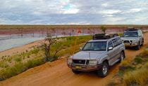 Outback scene with 4WD vehicles driving along a red dirt track past a wetland area. Photo credit: Richard O'Neill © Spirit Safaris