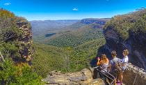A group of tour guests at a lookout with sweeping views of mountains and valleys. Photo © Stray Australia