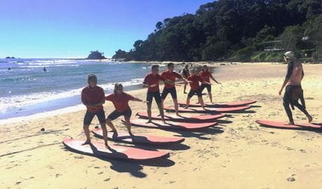 A group of students practice their surf stance on a beach with their Style Surfing School instructor. Photo credit: Gaz Morgan © Style Surfing School