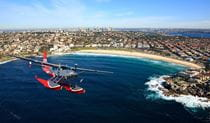 A Sydney Seaplanes plane flying over Bondi Beach. Photo: © Sydney Seaplanes
