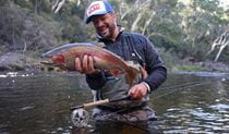Man holding a rainbow trout and fishing rod wading in a river. Photo: M. Tripet/The Fly Program