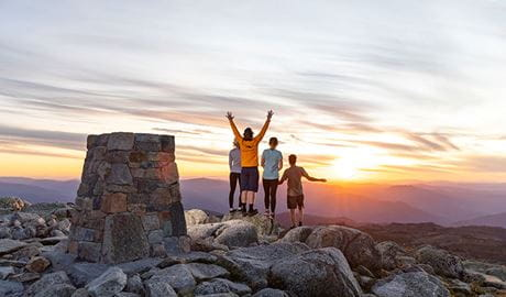 A group of 4 people stand near a rock cairn at the summit of Mount Kosciuszko at sunset. Photo © Thredbo Resort
