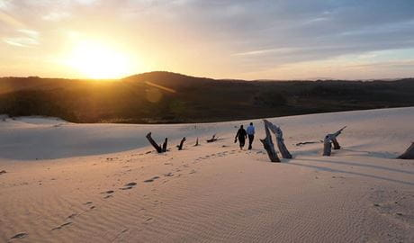 2 people walking over the sand dunes at Samurai Beach at sunset. Photo: Amy Robinson © Tomaree Coastal Adventures
