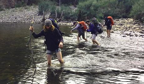 Hikers with backpacks make a river crossing in a wilderness setting. Photo credit: Adam Stewart © The Tops Conference Centre