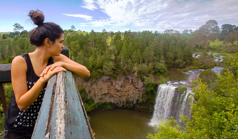 A young woman on a Via Travel Australia guided tour gazes out over a wide vista of bushland, river and waterfall at a lookout. Photo © Via Travel Australia