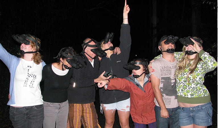 A group of 7 guided tour participants wearing night vision goggles in the dark. Photo credit: Wendy Bithell © Vision Walks Eco Tours