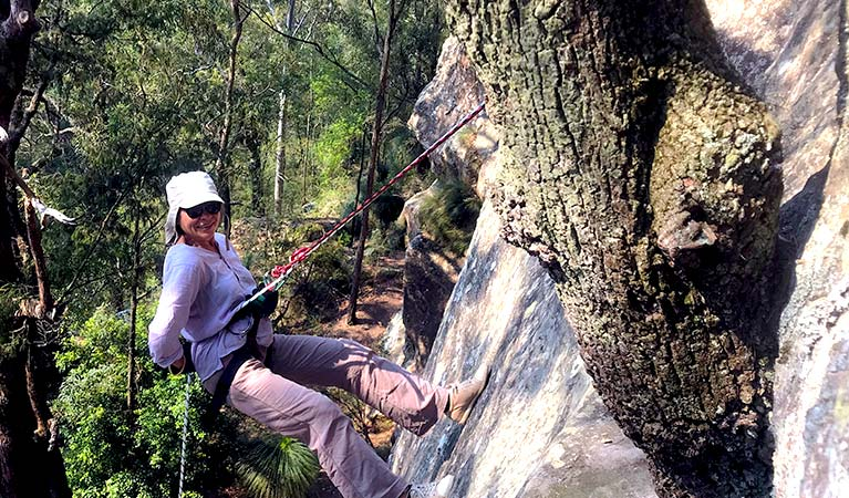 A woman abseils down a cliff surrounded by bushland in Watagans National Park. Photo © Walking Rivers