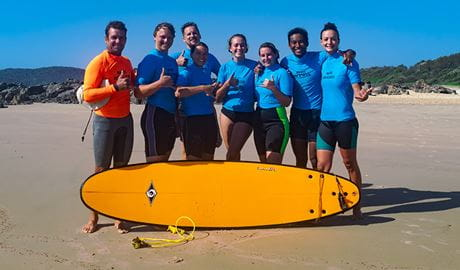 A group of surfers and their instructor pose with a surfboard on the beach. Photo credit: Annemieke Yperlaan © Waves Campground