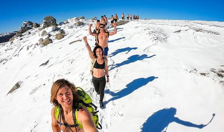 Trekkers, some dressed only in shorts, hike in a long line across a snowy alpine landscape in Kosciuszko National Park. Photo © Majell Backhausen
