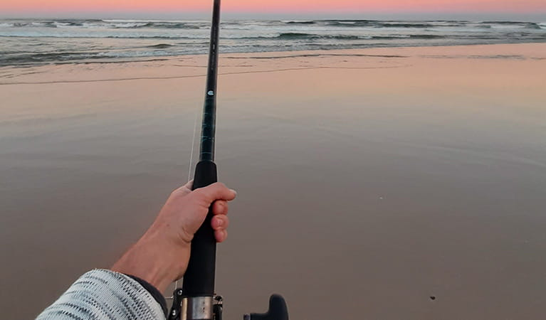 View of an angler's arm with a fishing rod and reel on a pristine sandy beach at twilight. Photo credit: Tim Williams © Wilderness Adventures
