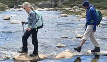 2 people crossing a river on a hiking tour in Kosciuszko National Park with Wilderness Sports. Photo: Bruce Easton © Wilderness Sports