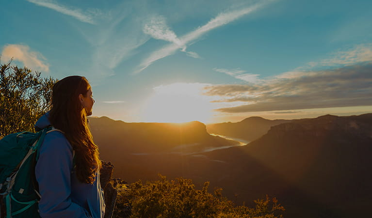 A young woman watches a dramatic sunset over the Blue Mountains.  Photo credit: Andy Lloyd © Women Want Adventure
