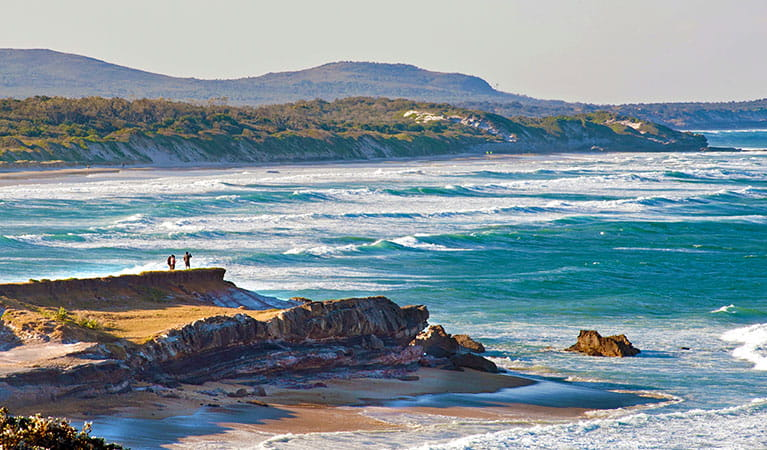 Distant figures on a rocky outcrop, with beaches and headlands stretching into the distance. Photo credit: Sandy Scheltema © Yuraygir Walking Experiences