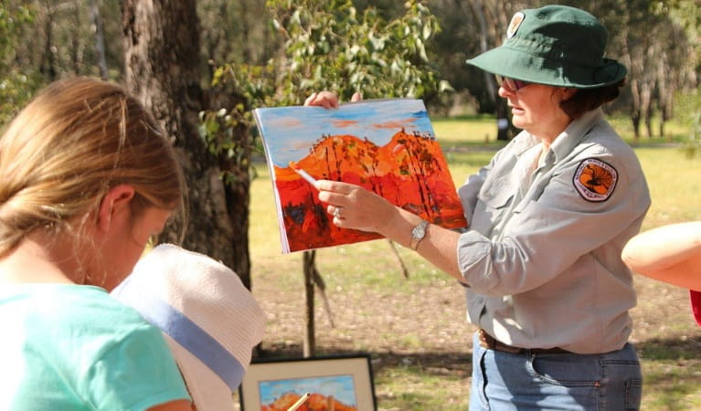 An NPWS ranger guiding children to paint the landscape in Warrumbungle National Park. Photo: S Brookhouse/OEH