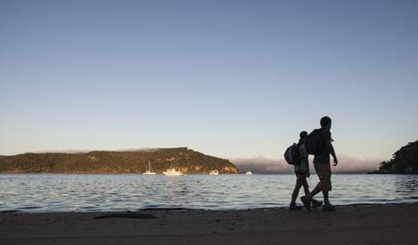 2 people walking towards Barrnejoey Headland in Ku-ring-gai Chase National Park. Photo: D Finnegan/DPIE