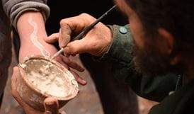 An Aboriginal Discovery ranger paints a snake in ochre on a boy's arm. Photo: Paul Watkins/OEH