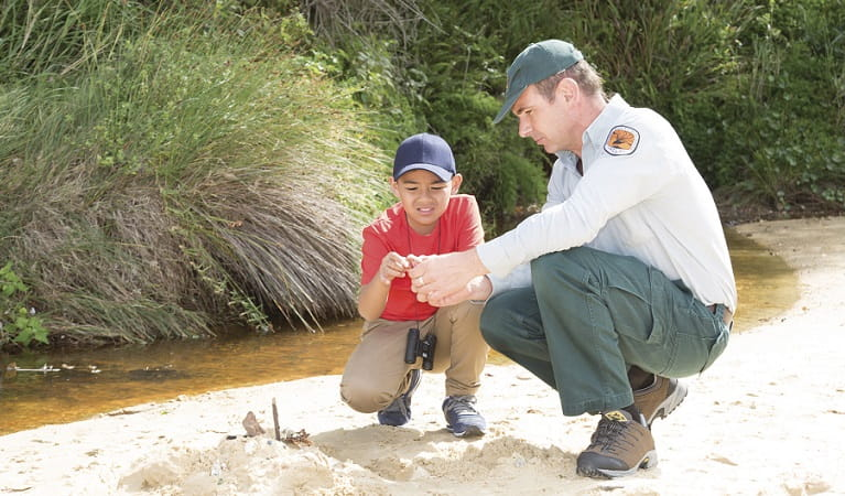 A NSW National Parks ranger and a boy look at a plant by a creek. Photo: Rosie Nicolai/OEH