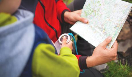 Child holding a compass and reading a map. Photo: Zhukovvvlad/Shutterstock