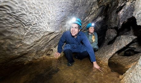 Two people crawling through a cave during the River Odyssey adventure caving guided tour. Photo: Boen Ferguson
