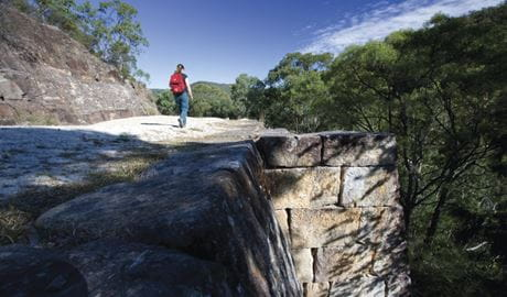 A woman walks along the convict-built Great North Road in Dharug National Park. Photo: N Cubbin/OEH